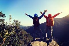 Riuscito viaggiatore con zaino e sacco a pelo due a braccia aperte alla montagna fotografia stock