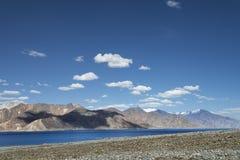 Riva dei ciottoli del lago a distanza dell'alta montagna Fotografie Stock Libere da Diritti