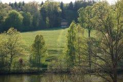 Riva del lago con il prato ed alberi che cercano capanna nel fondo fotografia stock