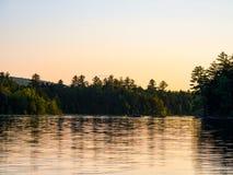 Riva del lago mountain, Forest Glowing al tramonto immagini stock libere da diritti