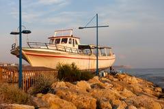 Riva di mar Mediterraneo nel Cipro con una vecchia barca Immagini Stock
