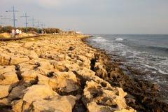 Riva di mar Mediterraneo unione nel Cipro, Europa, con le pietre e le onde bianche Fotografia Stock