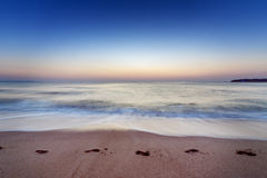 Riva di mare con una spiaggia sabbiosa con le tracce di piedi Immagine Stock