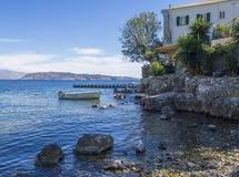 Riva di mare del ciottolo e la Casa Bianca in Kalami, precedente residenza di Lawrence autori e di Gerald Durrell britannici e immagine stock