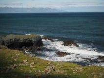 Riva di mare erbosa con il fondo della montagna immagine stock