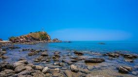 Riva di mare di pietra con il faro fotografie stock libere da diritti