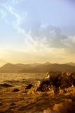 Riva di mare rocciosa e cielo drammatico al tramonto Immagine Stock