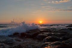 Riva di mare rocciosa nei raggi del cielo di tramonto Battiti di Wave sulla riva di mare Immagine Stock Libera da Diritti