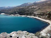 Riva e montagne del ‹del †del ‹del †del mare al giorno soleggiato Fotografie Stock Libere da Diritti