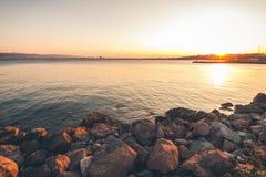 Riva rocciosa al tramonto con la siluetta della città e del mounta Immagini Stock