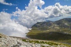 Rivage avec des nuages dans la montagne photo stock