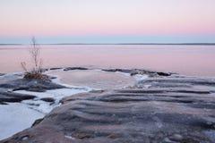 Rivage congelé de lac de roche au crépuscule Photographie stock libre de droits