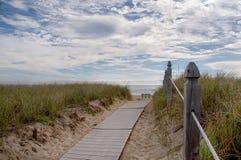 Rivage d'océan avec un banc et un chemin à lui Photo stock