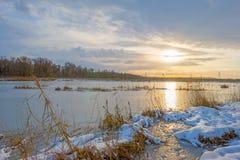 Rivage d'un lac congelé dans un domaine neigeux au soleil Image libre de droits