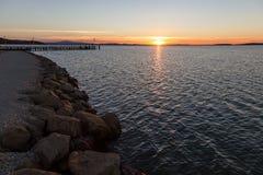 Rivage de lac au coucher du soleil, avec de grandes roches dans le premier plan et le beaut Photographie stock