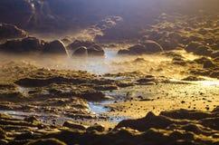 Rivage de plage rocheuse à la lumière de nuit Photographie stock libre de droits