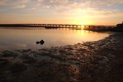 Rivage de rivière et pont en bois pendant le coucher du soleil Photographie stock
