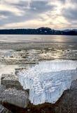 Rivage exposé sous la glace de fonte Fermez-vous vers le haut de la vue pour encadrer entre la glace et l'eau foncée photographie stock libre de droits