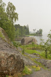 Rivage rocheux avec les buissons, l'herbe et les arbres sur le rivage du pro Photographie stock