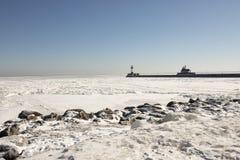 Rivage rocheux le long du lac Supérieur congelé avec le pilier et les phares Photographie stock libre de droits