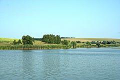 Rivage vert d'un grand étang Photographie stock