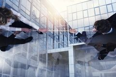 Rival business man and woman compete for the command by pulling the rope. double exposure. Rival business men and women compete in office for the command by stock photo