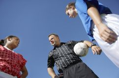 Rival Female Players In Front Of Soccer Referee. Rival female soccer players standing in front of referee against sky Royalty Free Stock Images