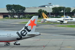 Rival low cost carriers Jetstar Asia and Tigerair at Changi Airport. SINGAPORE - DECEMBER 23: Rival low cost carriers Jetstar Asia and Tigerair at Changi Airport royalty free stock photos