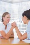 Rivaliserande affärskvinnor som har en armbrottning Arkivfoton