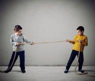 Rivaliteit van twee broers met een kabel royalty-vrije stock foto