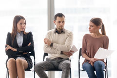 Rivalry and competition between businesspeople, applicants waiti. Male and female candidates waiting for interview, sitting together in a row, looking at each Royalty Free Stock Photo