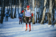 Rivalry young athlete skiers race in winter forest classic style Stock Image