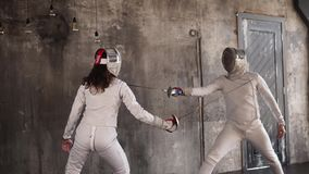 Rivals are actively engaged in fencing a man and a woman are cheating each other
