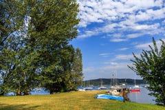 Rive del lago Maggiore con le piante, il sole e le barche Fotografia Stock