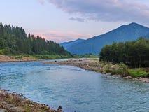 Rive di ampio fiume della montagna coperto di pietre vicino alla foresta sui precedenti delle gamme di alta montagna Fotografia Stock