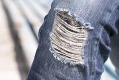 Riven sönder jeans på knäet av flickatonåringen royaltyfri fotografi