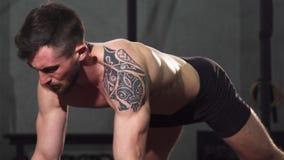 Riven sönder muskulös tatuerad man som utarbetar på idrottshallen lager videofilmer