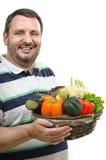 Rivenditore allegro con un canestro delle verdure Immagini Stock