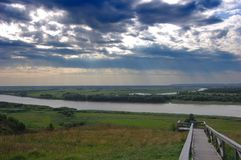 River. View of the river valley and the stairs leading down with stormy sky and the rays of the sun visible through the clouds Stock Photo