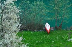 By the river. A red and white canoe resting by the river Royalty Free Stock Image