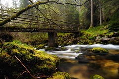 River. An old bridge which crosses a stream with moss-covered stone Stock Image