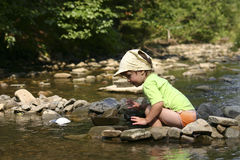 By the river. Kid playing with stones and water by the mountain river Royalty Free Stock Photos