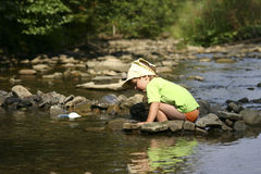 By the river. Kid playing with stones and water by the mountain river Royalty Free Stock Photography