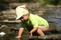 By the river. Kid playing with stones and water by the mountain river Stock Image