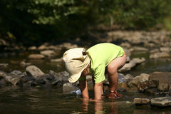 By the river. Kid playing with stones and water by the mountain river Stock Photography