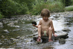 By the river. Kid playing with stones and water by the mountain river Royalty Free Stock Photo