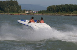 River action. Two young men speeding up the river royalty free stock photography
