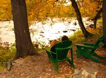man relaxing river adirondack chairs Royalty Free Stock Photo