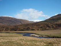River Affric in Glen Affric, Scotland in spring. River Affric in Glen Affric, with snow covered moutains, Scotland in may Royalty Free Stock Photos