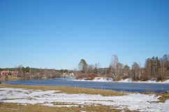 A river in the afternoon hours. A river near a small village in spring in Dalarna Stock Photos